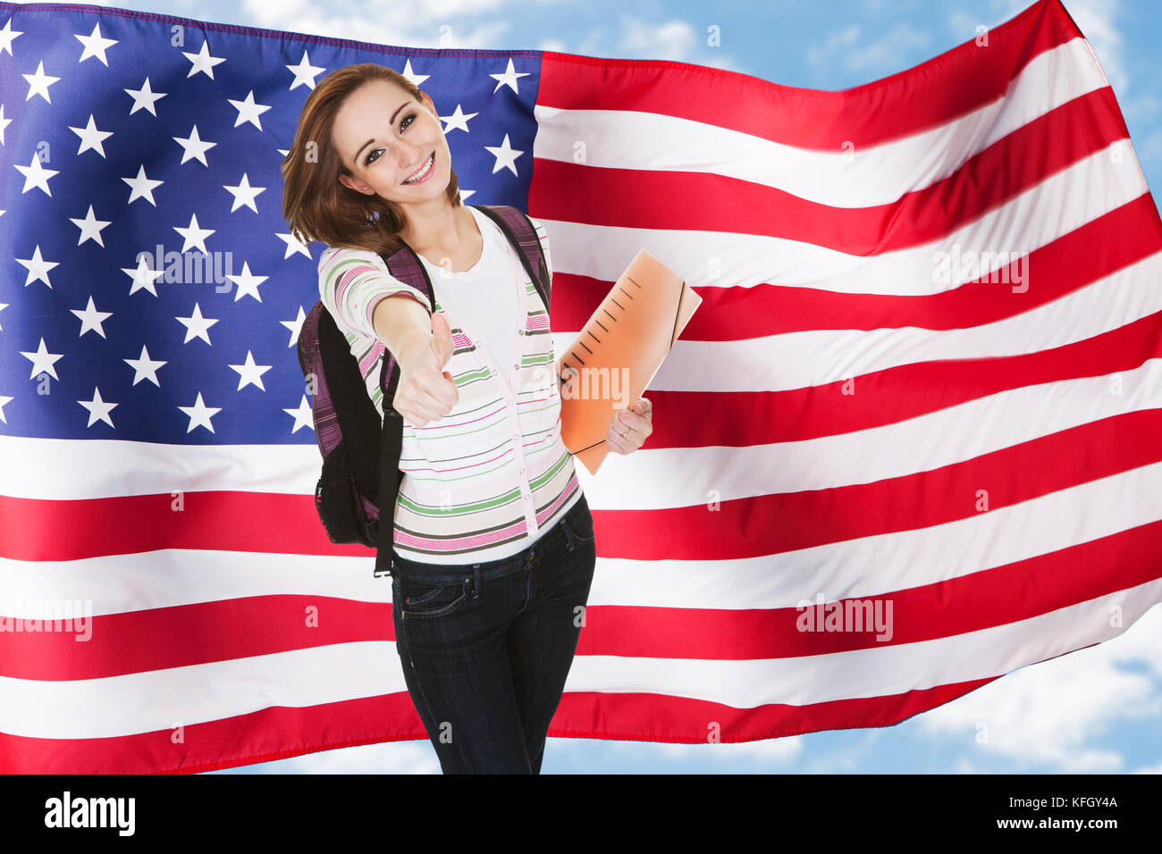 Young American Female Student Gesturing Thumb Up Sign - Stock Image