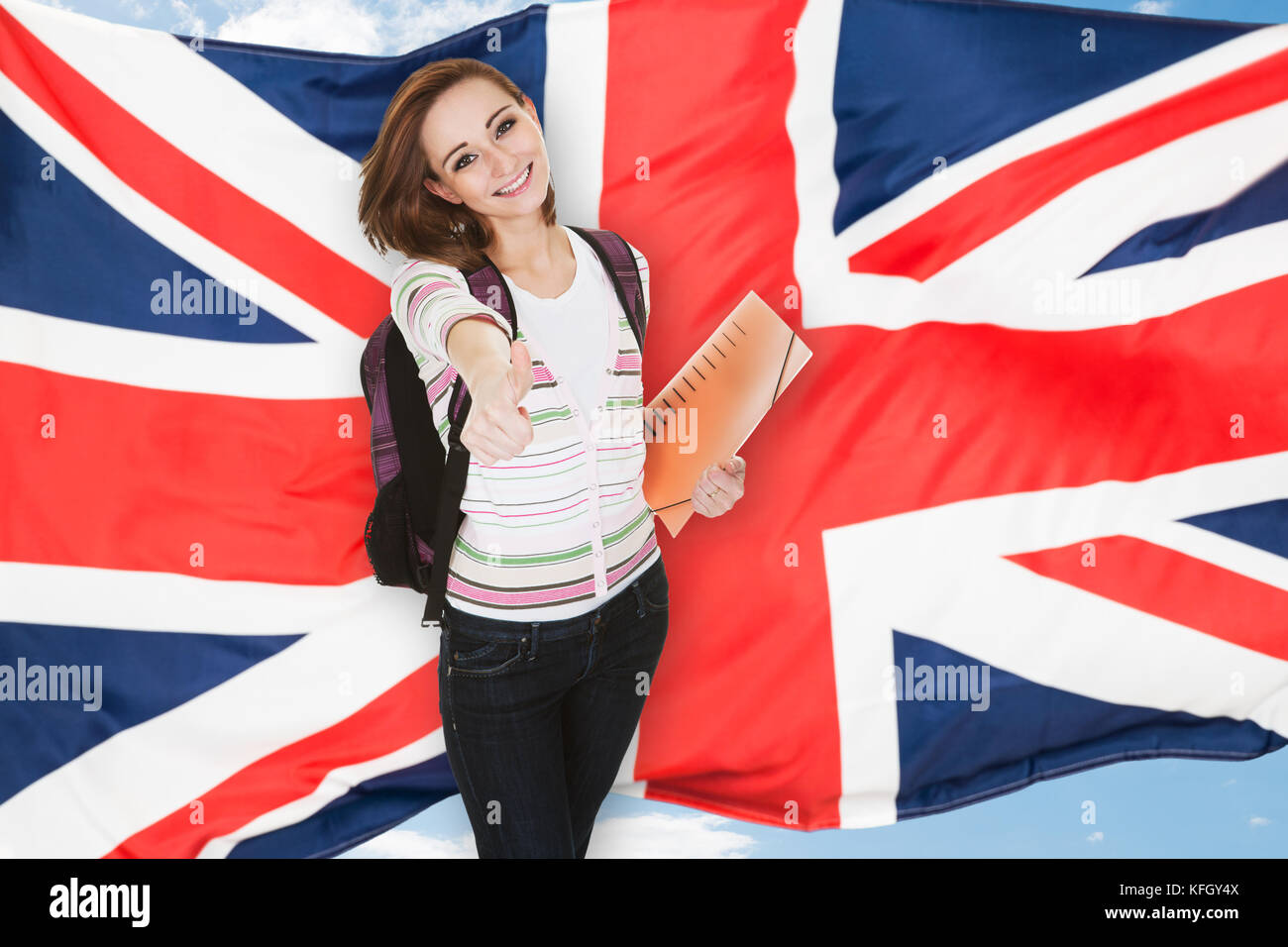 Young Female Student Gesturing Thumb Up In Front Of British Flag - Stock Image