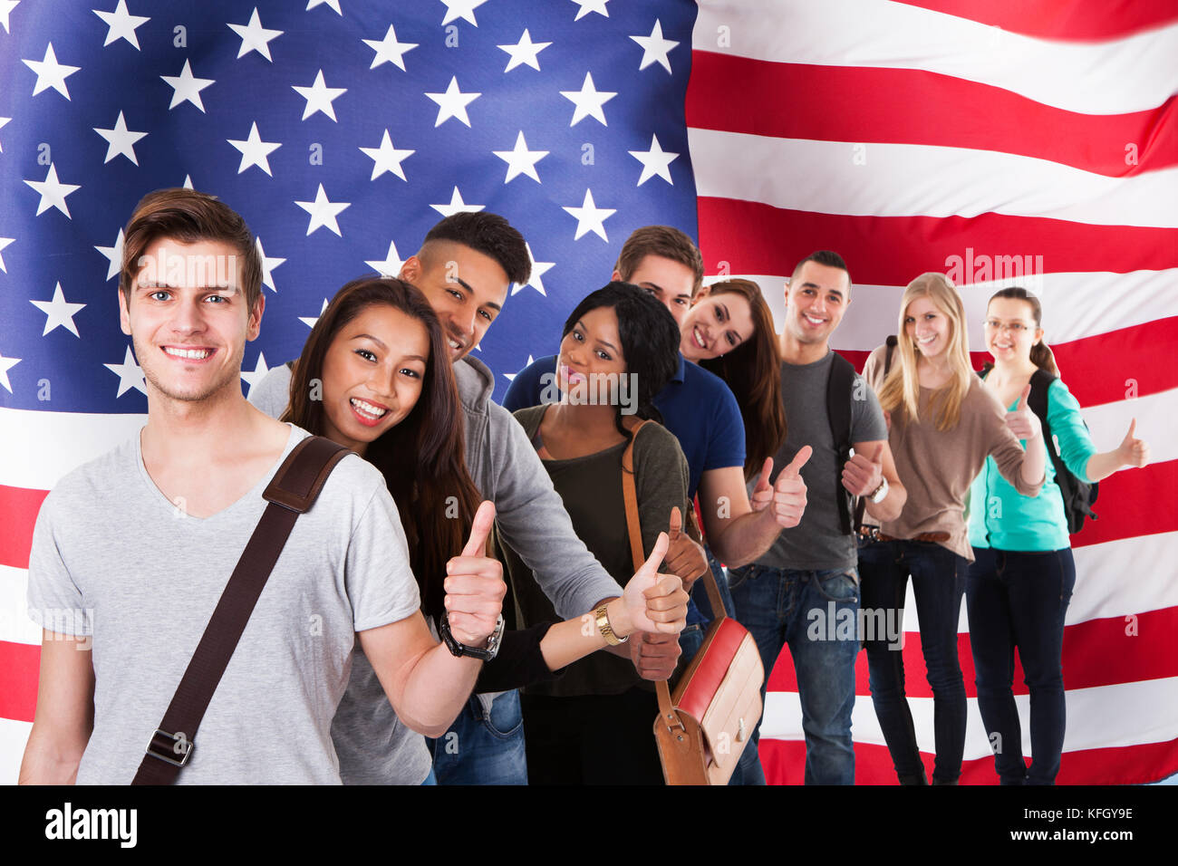 Group Of Diverse Students Standing In Front Of American Flag Showing Thumb Up - Stock Image