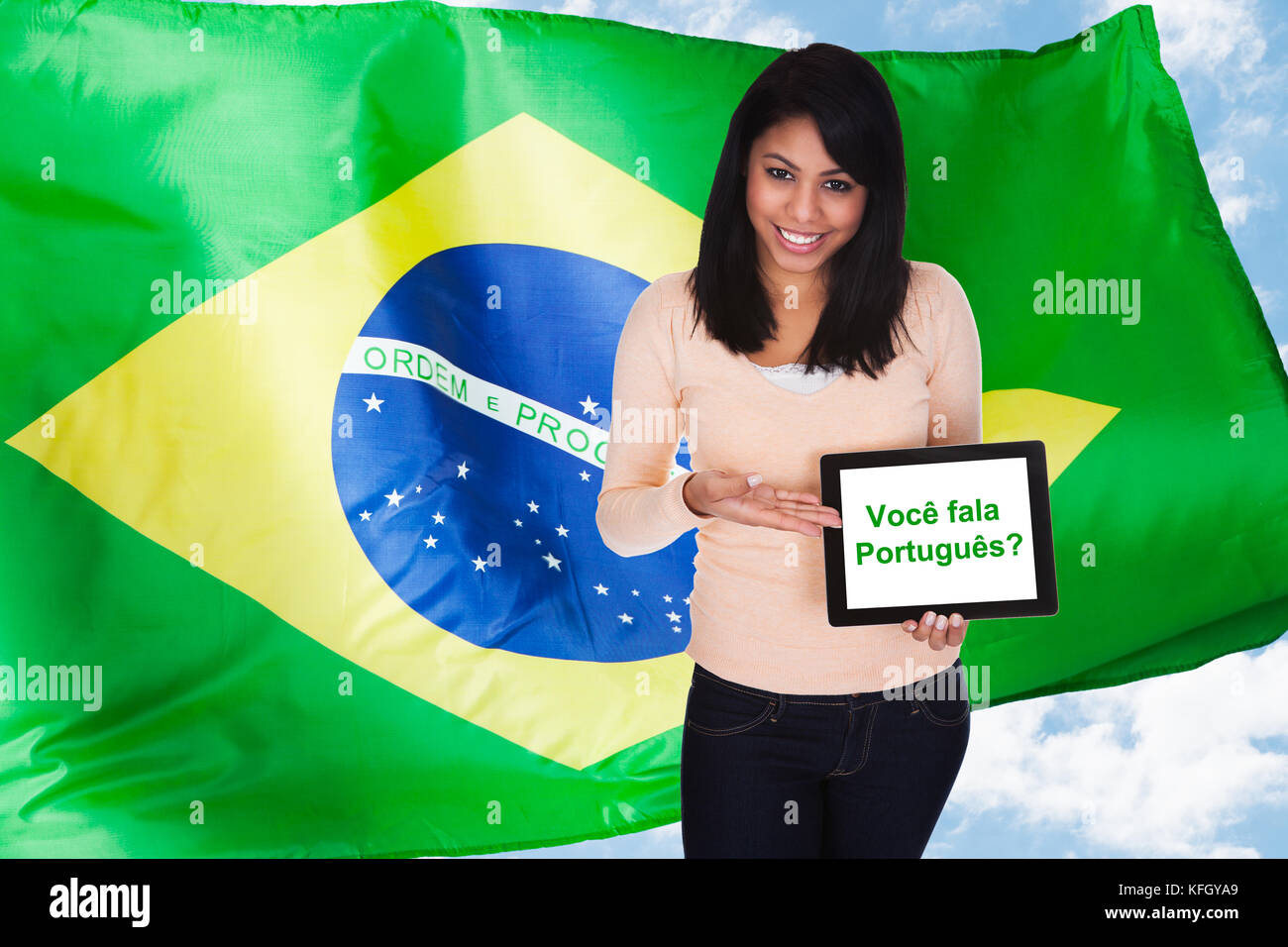 Young Woman Holding Digital Tablet Asking Do You Speak Portuguese In Front Of Brazilian Flag Stock Photo