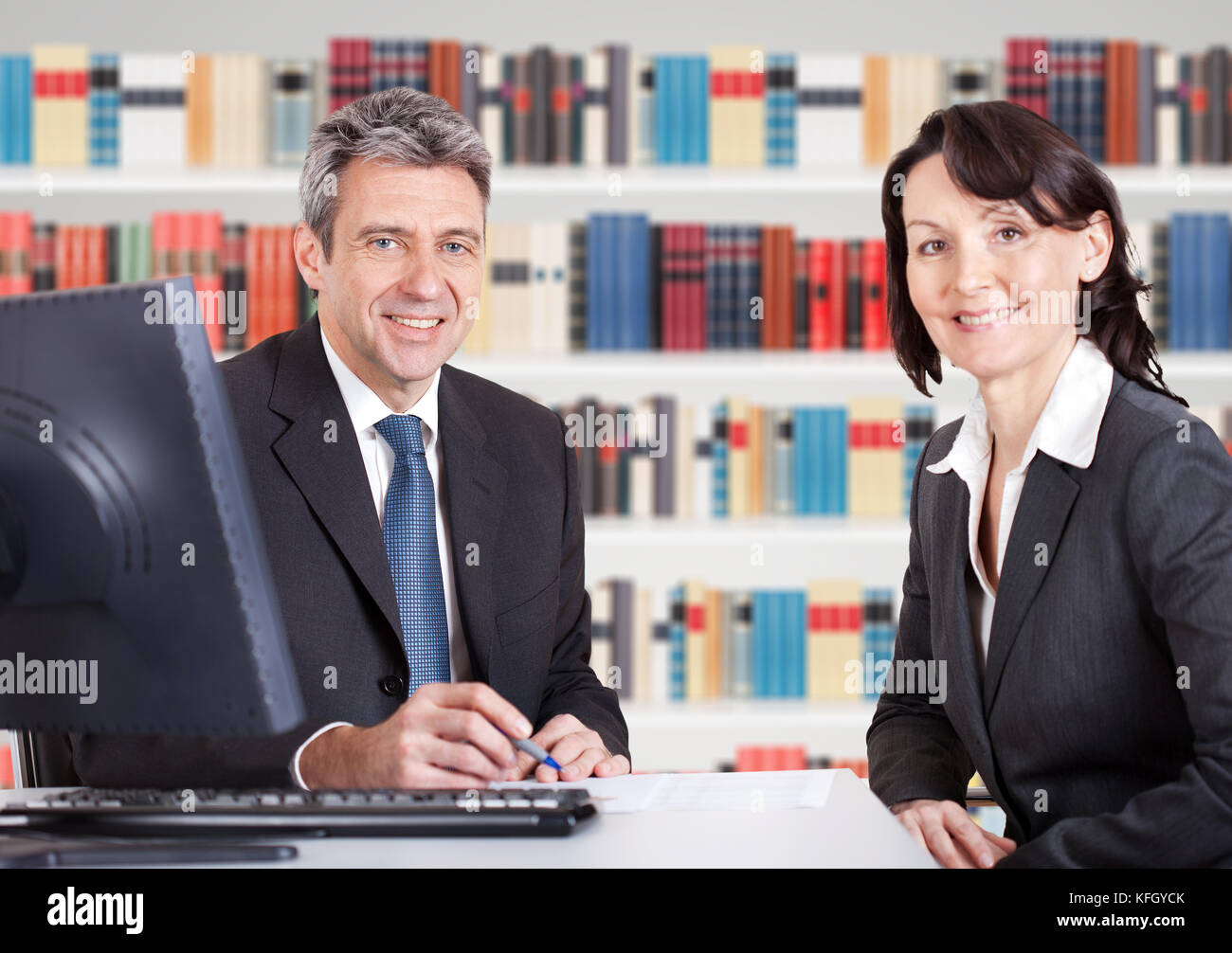 Two Happy Mature Businesspeople Sitting At Office Desk - Stock Image