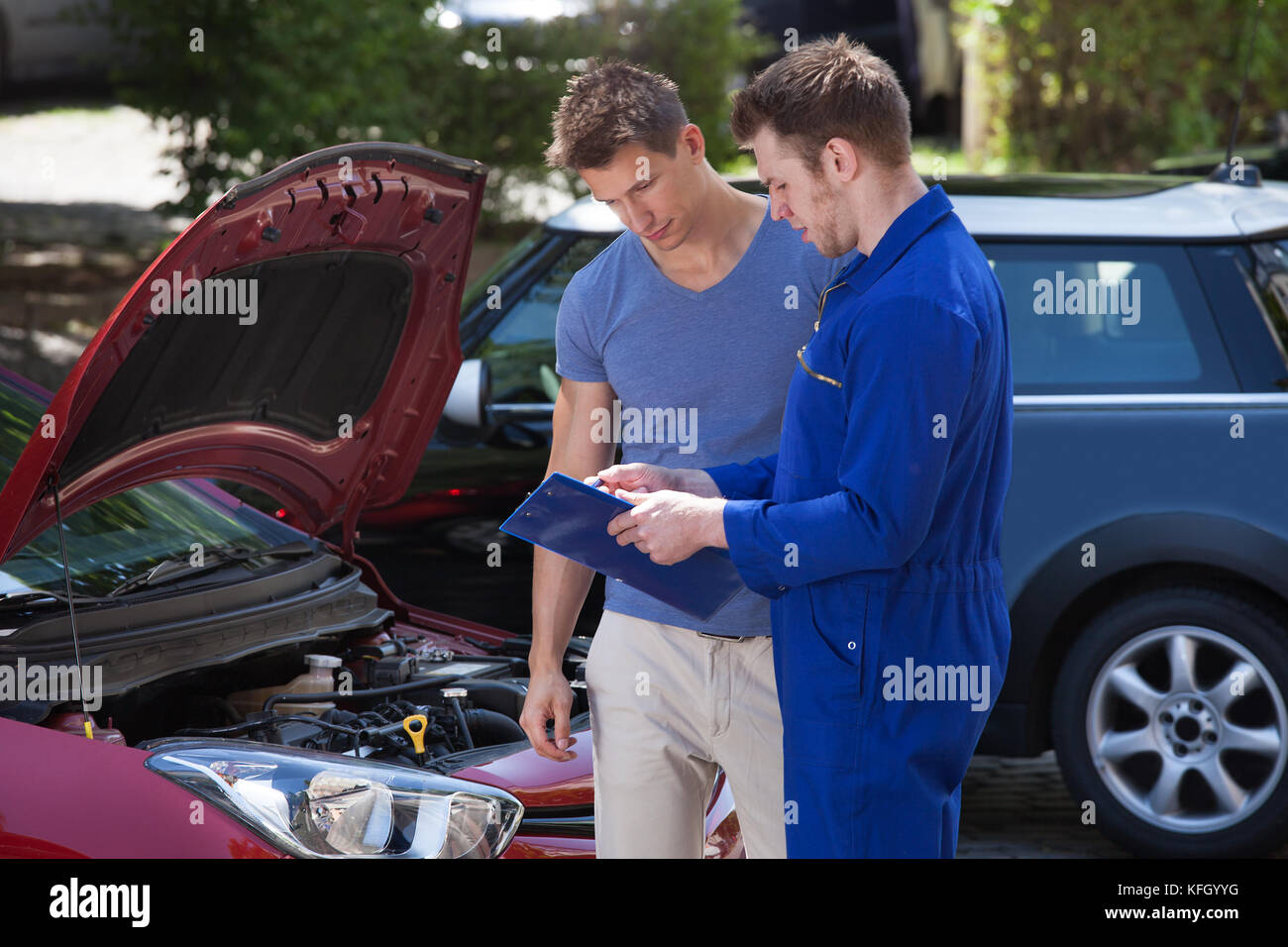 Young mechanic showing clipboard to customer by breakdown car - Stock Image