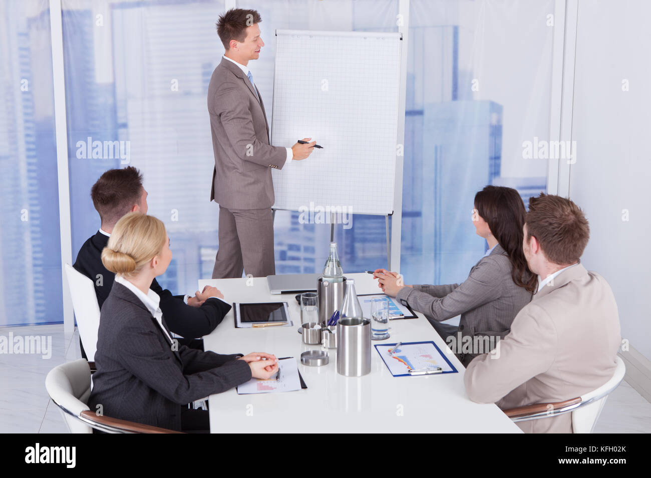 Young businessman giving presentation to colleagues at office - Stock Image