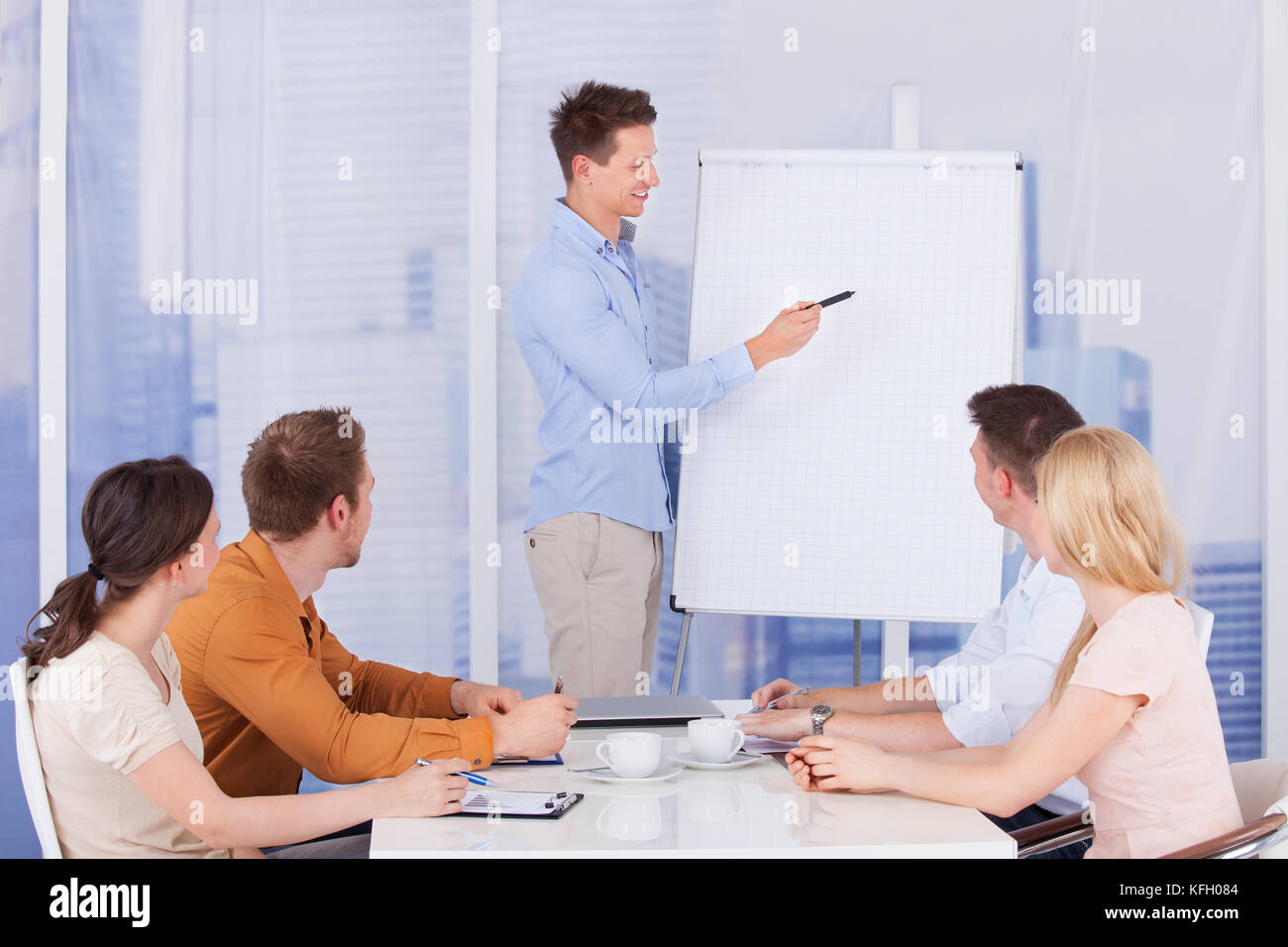 Young businessman giving presentation to colleagues in office - Stock Image