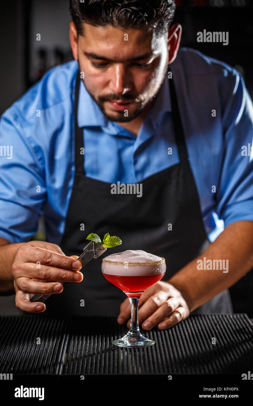 Bartender is decorating cocktail with mint leaf - Stock Image