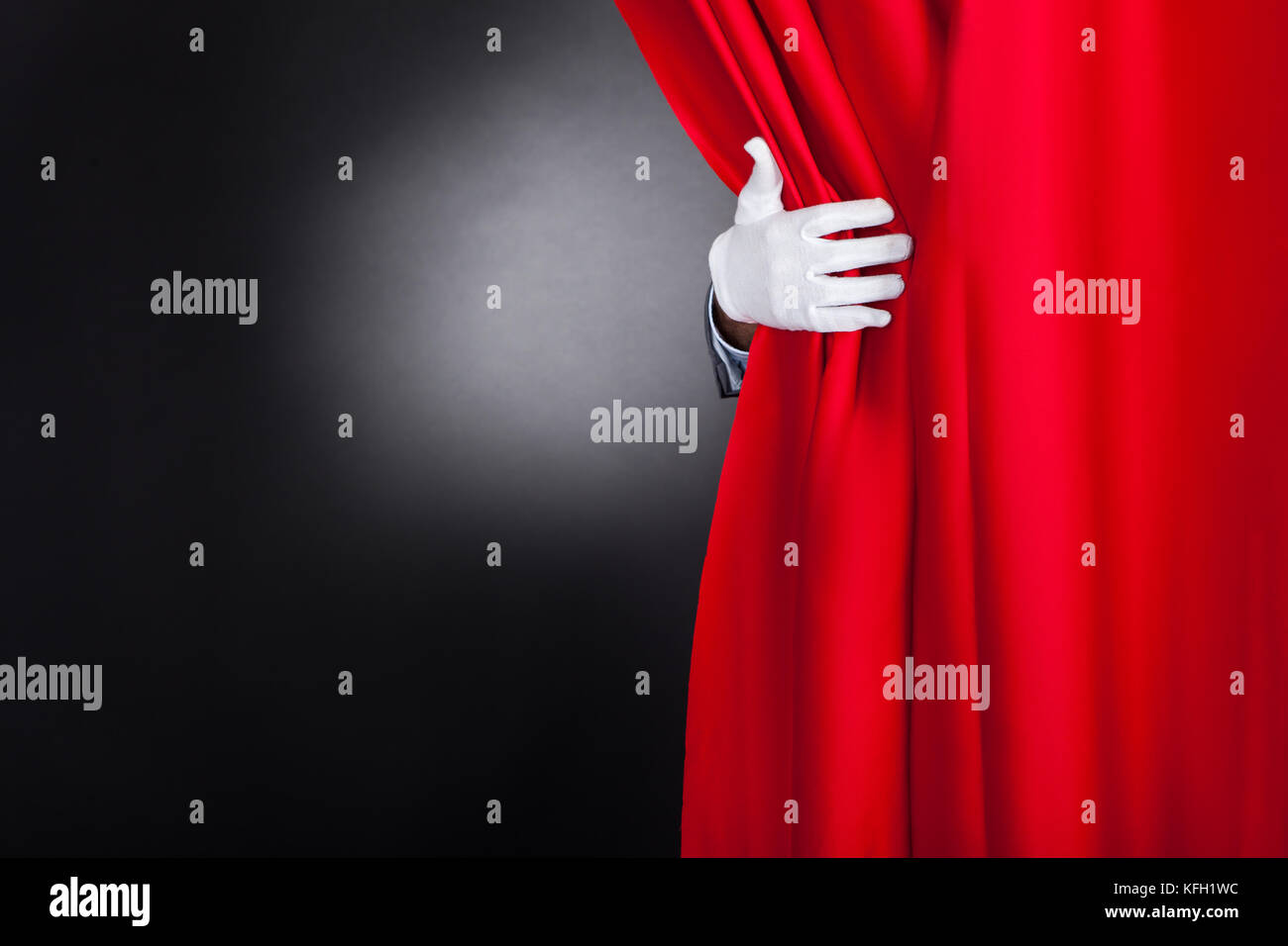 Cropped image of magician opening red stage curtain - Stock Image