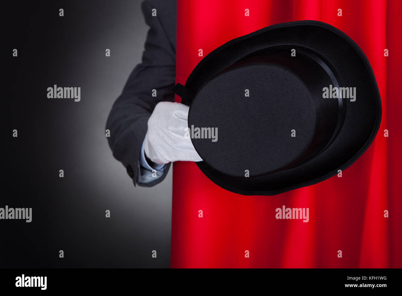 Cropped image of magician holding hat behind stage curtain - Stock Image