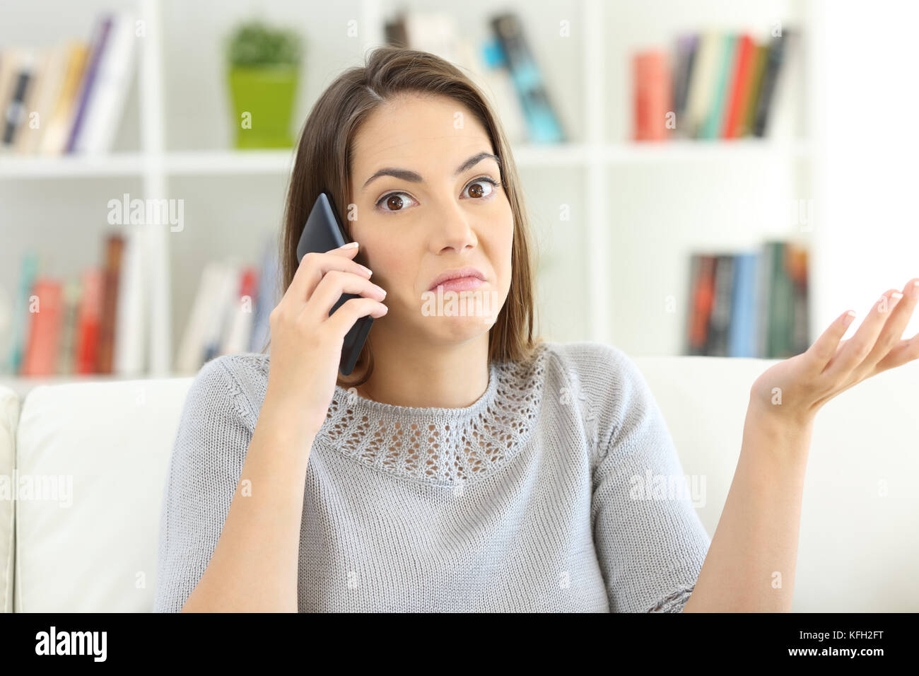 Confused customer being ignored calling custom service and looking at you sitting on a sofa at home - Stock Image
