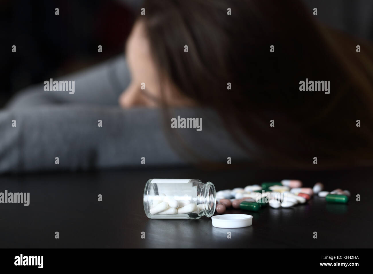 Close up of a woman lying dead after overdose of pills - Stock Image