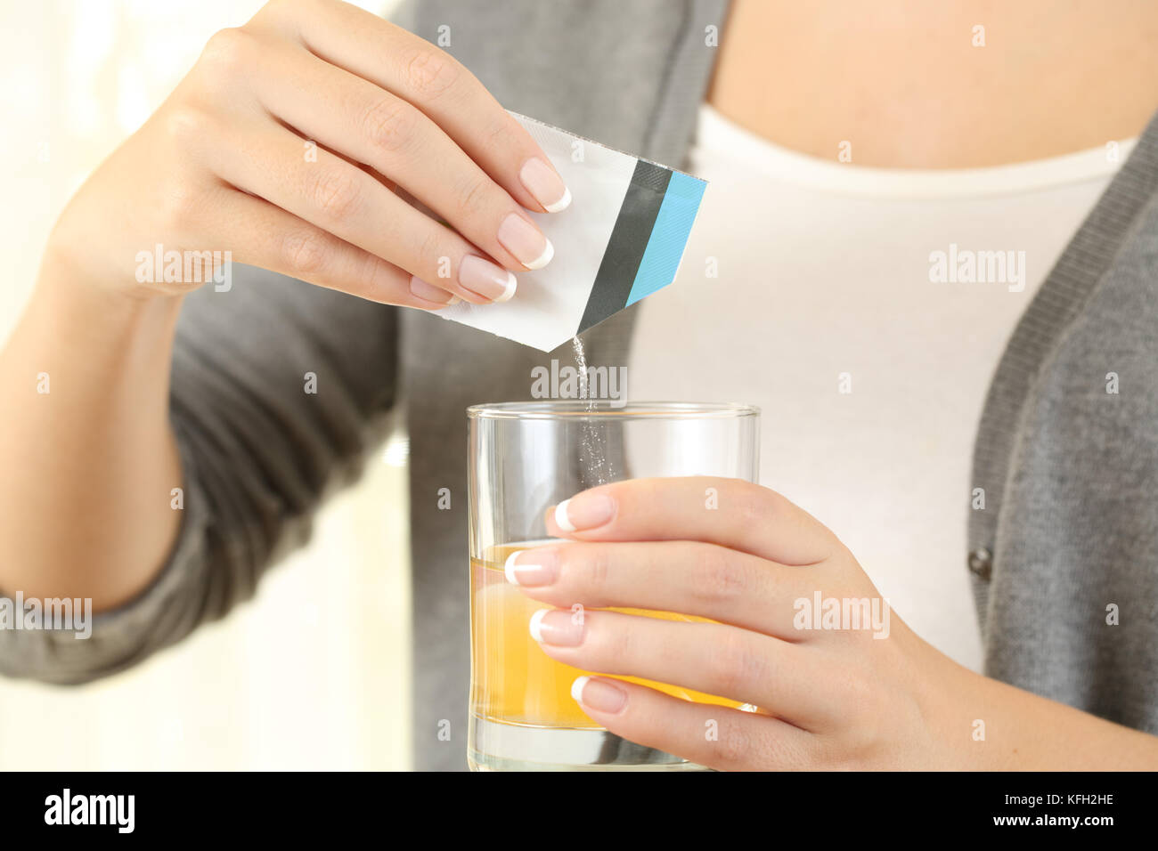 Close up of a woman preparing a mucolytic bag medicine on a glass of water - Stock Image