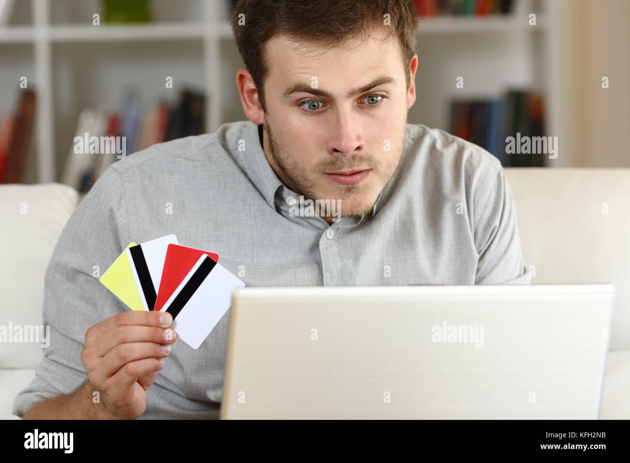 Stressed compulsive gambler gambling on line sitting on a sofa at home - Stock Image