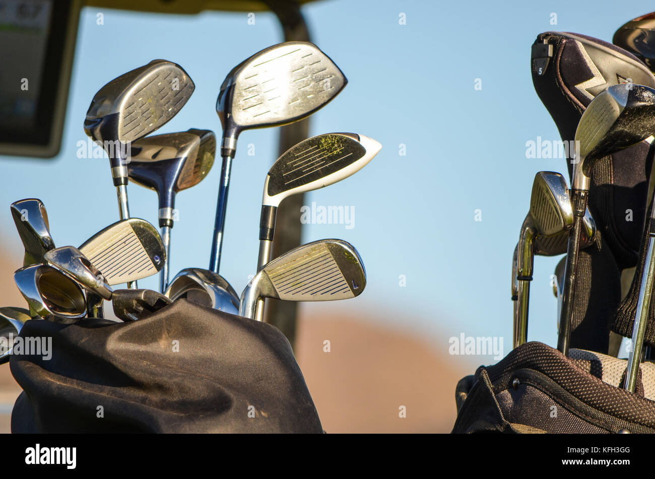 two golf bags with clubs on back of golf cart - Stock Image