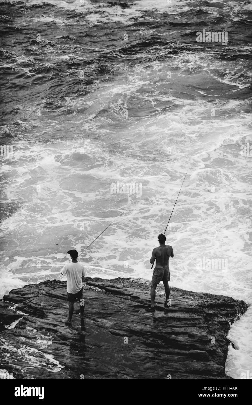 Two men stand on a rock in rough water fishing along the Bondi to Coogee coastal walk in Sydney, Australia. Stock Photo