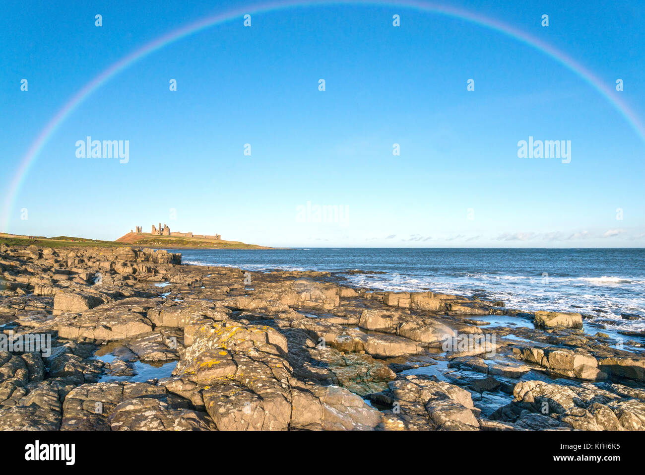 Rainbow over Dunstanburgh Castle - Stock Image
