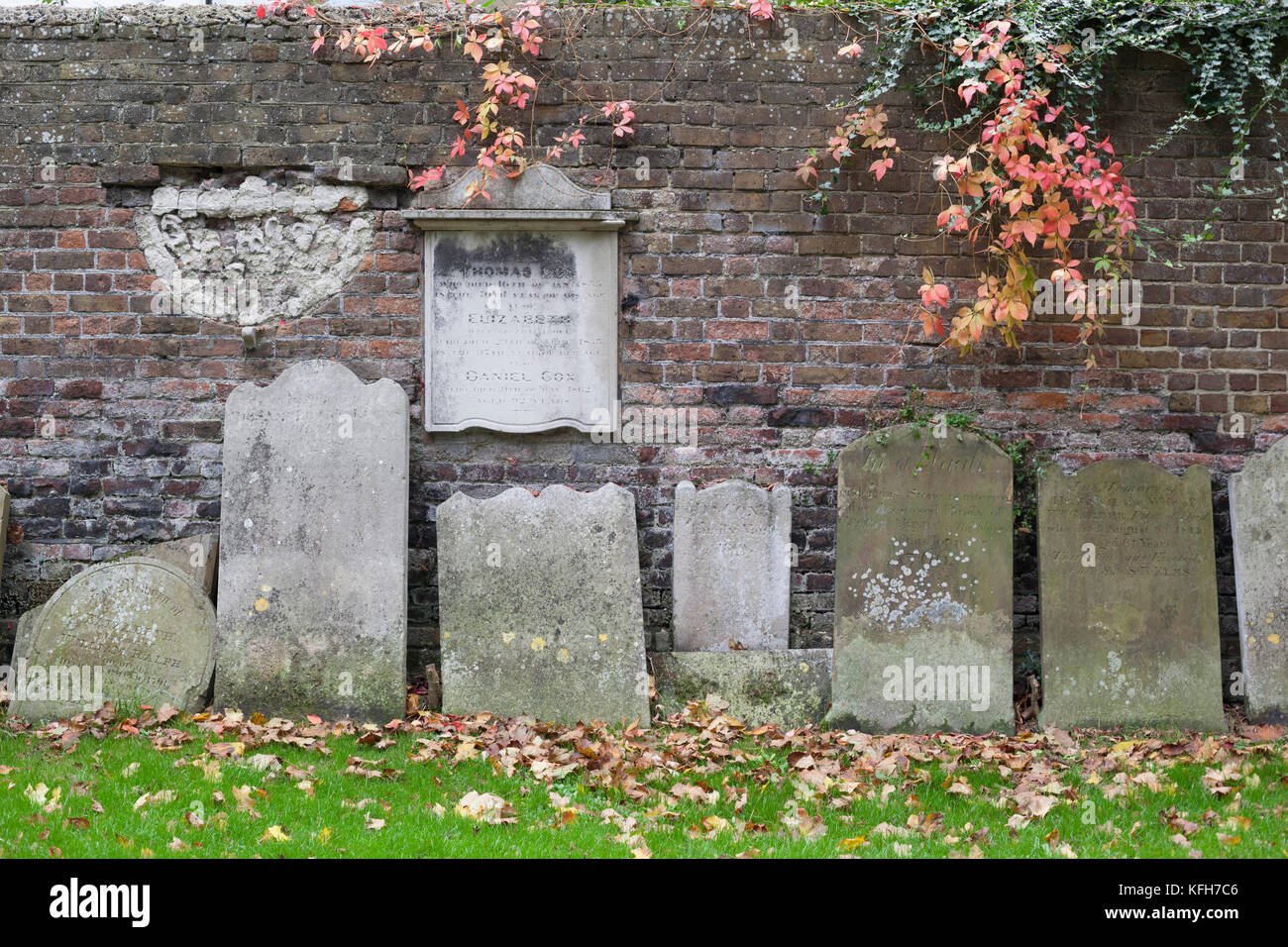 Gravestones stacked around edge of park behind St George's Deal church in autumn, Deal, Kent, England, United - Stock Image