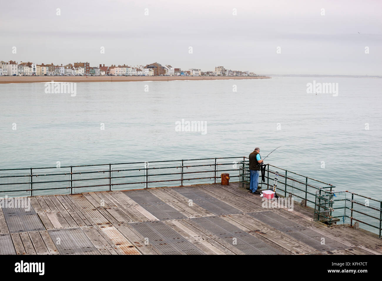 Fisherman fishing off Deal Pier with Deal seafront in mist behind, Deal, Kent, England, United Kingdom, Europe - Stock Image
