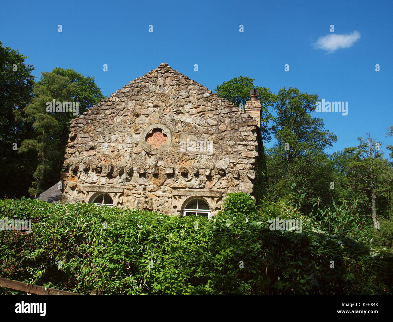 A cottage with an old stone wall facade situated on its own land amongst trees, shrubs and blue skies.          - Stock Image
