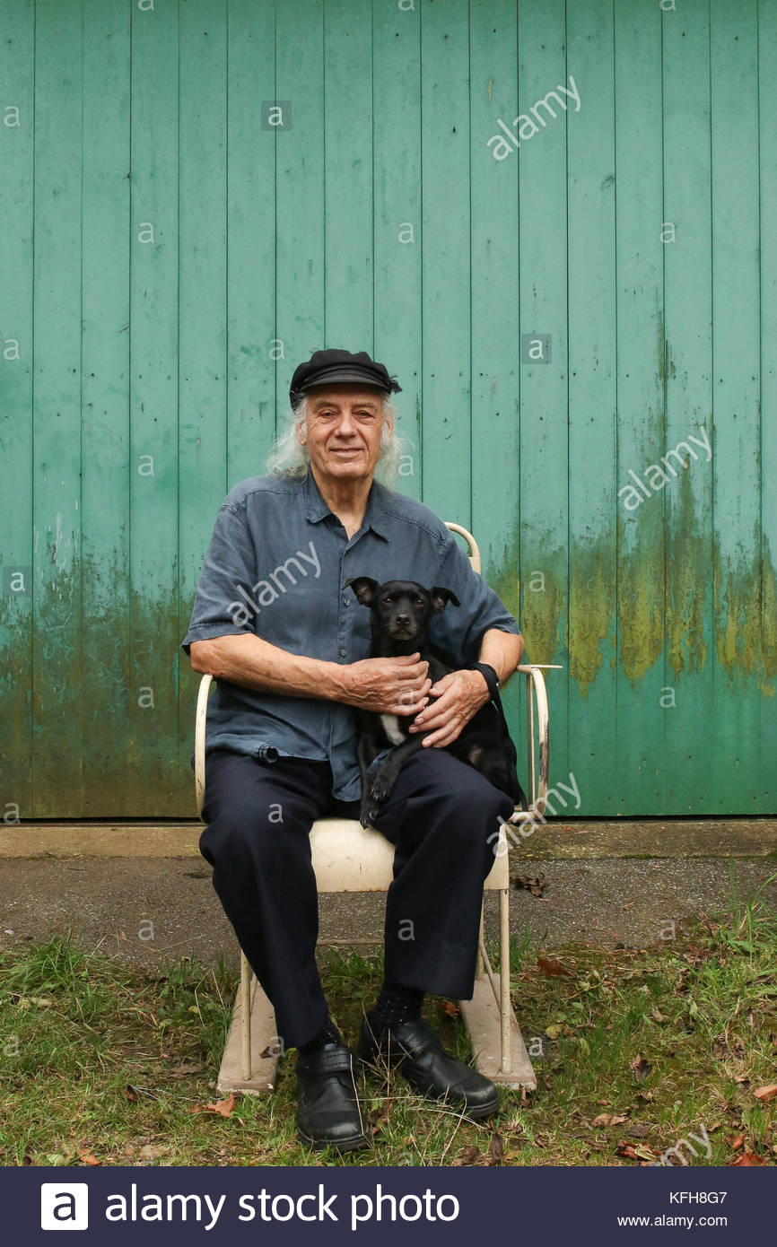 Man aged 80 - 90 sitting with his dog, outside. - Stock Image