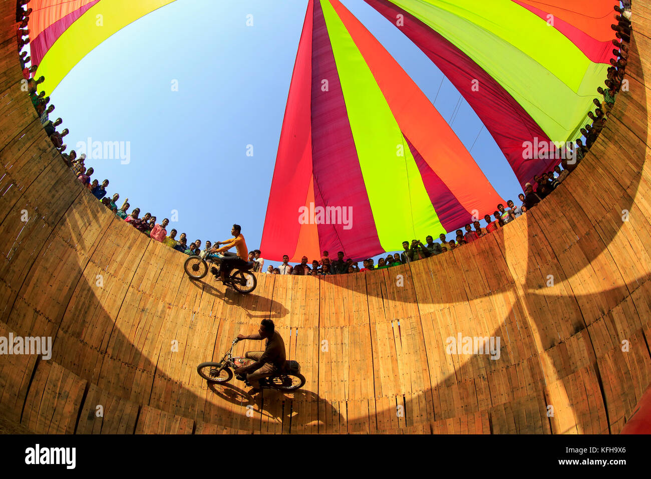 A dare devil motorbike show where the biker takes life risk running his bike along the wall of a large wooden well Stock Photo