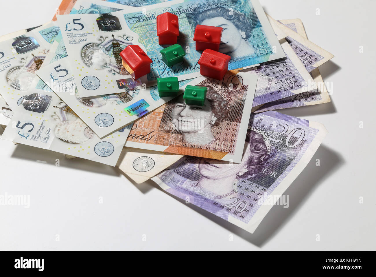 New British £5 and £10 notes with red and green monopoly houses and hotels - Stock Image