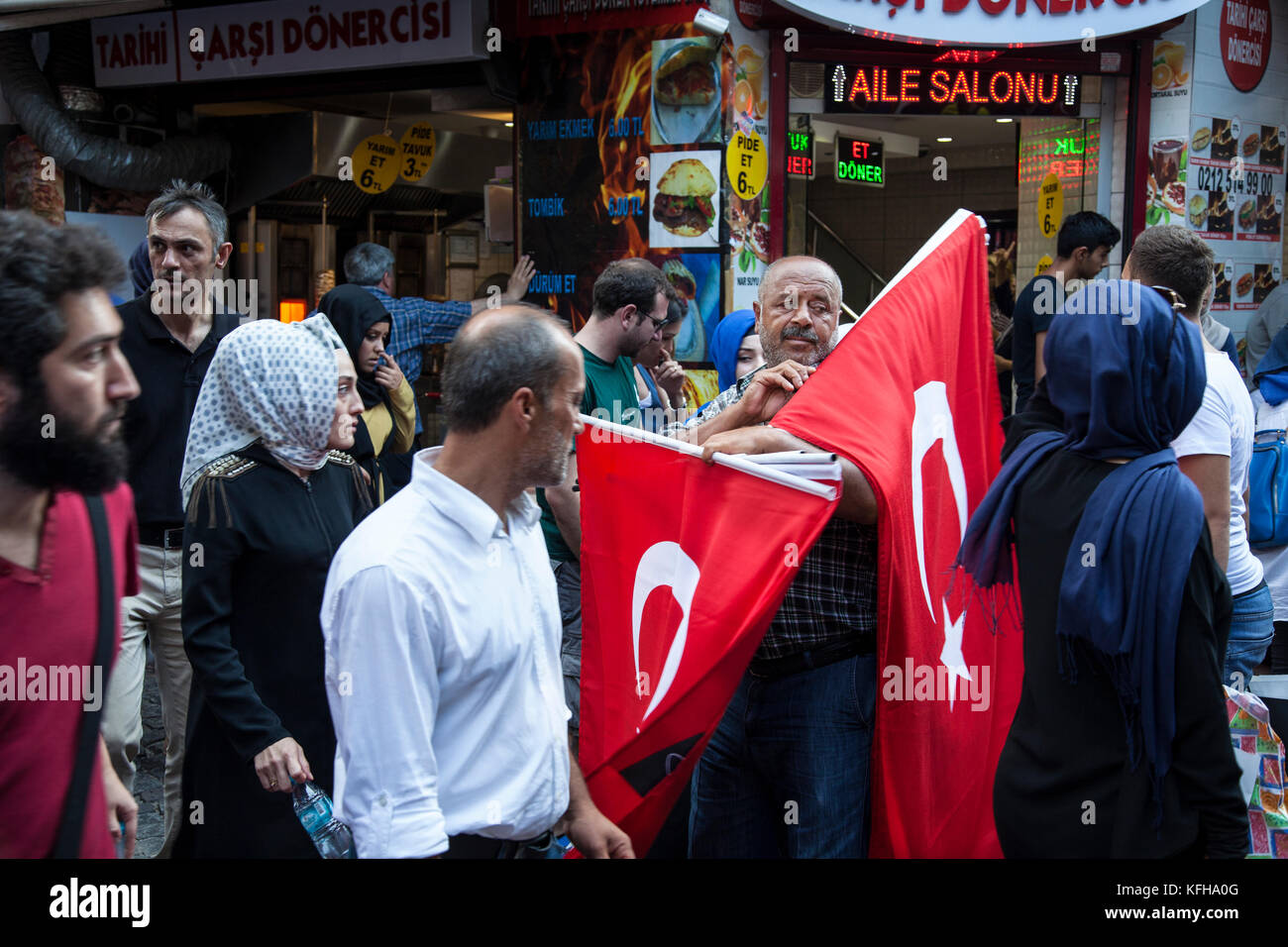 A man sells Turkish National flags on the street outside the spice market in Istanbul, Turkey. - Stock Image