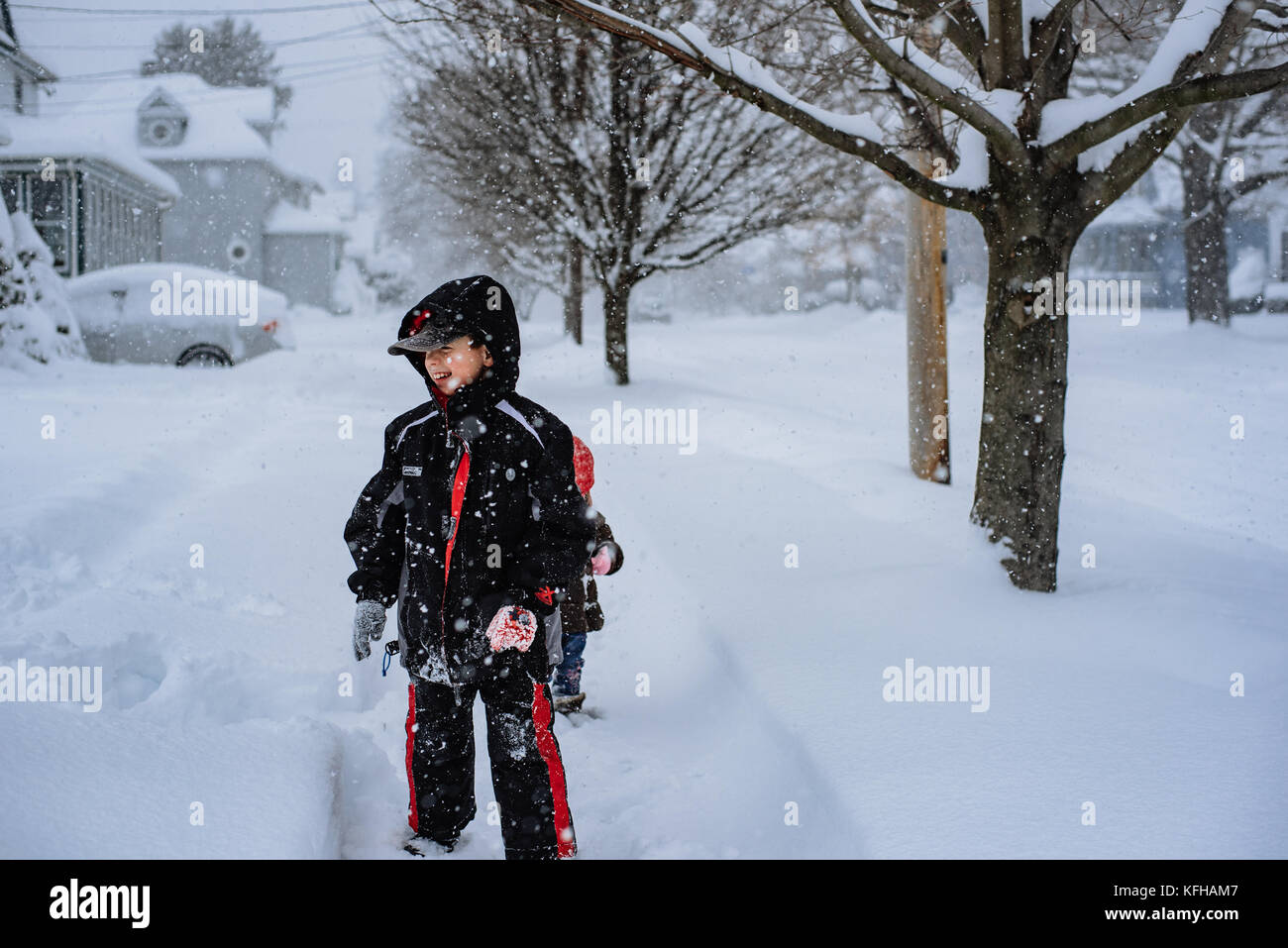 10-11 year old boy standing in snow - Stock Image