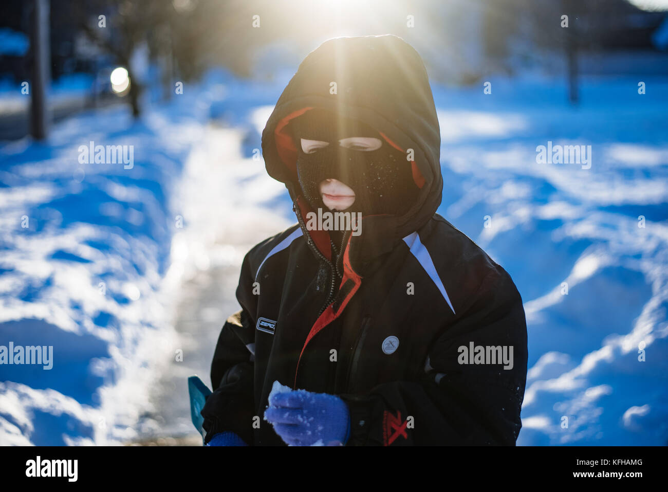 10-11 year old boy standing in snow with ski mask Stock Photo