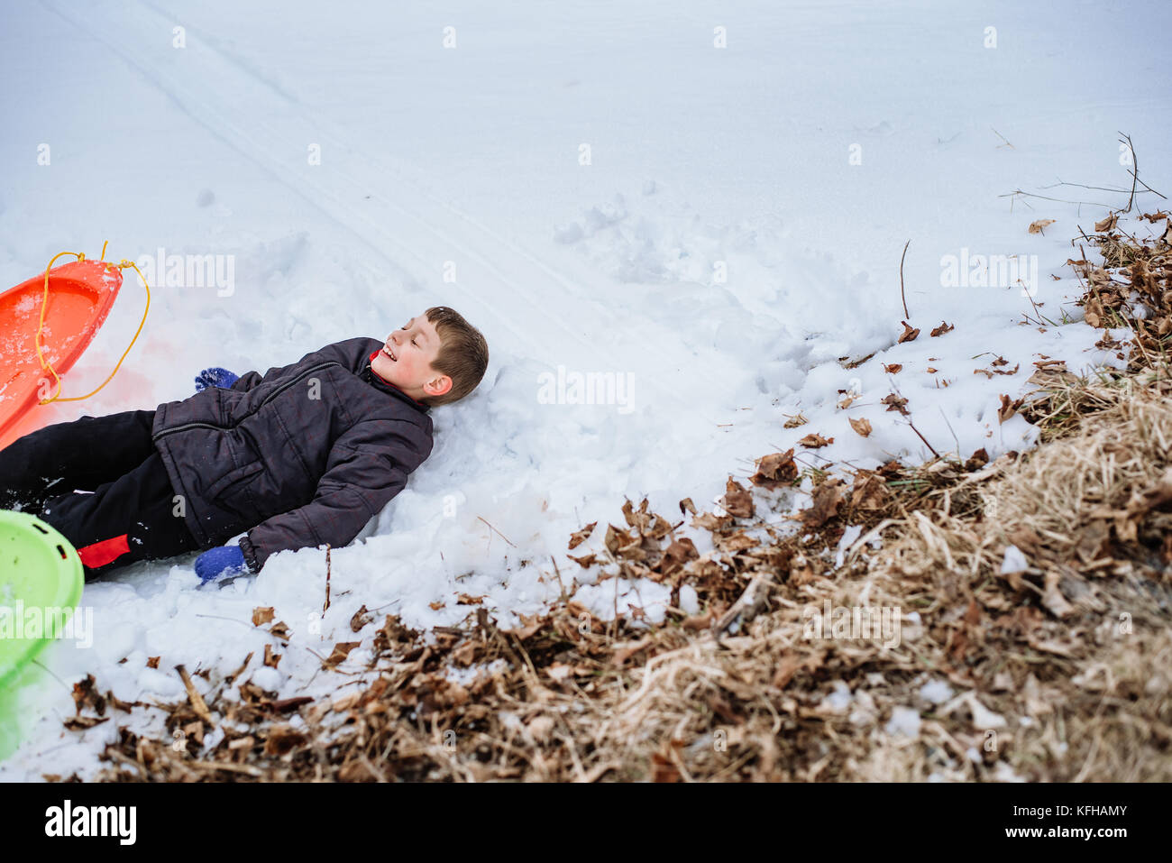 Boy laying in the snow - Stock Image