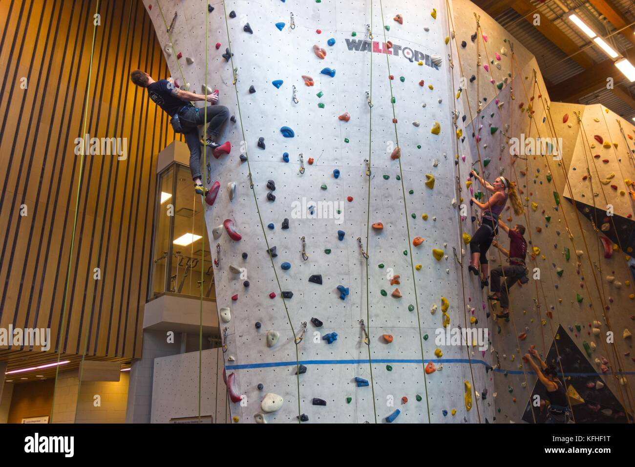 Climbers Scaling Vertical Rock Climbing Wall in Elevation Place Recreation Facility in Canmore Alberta - Stock Image