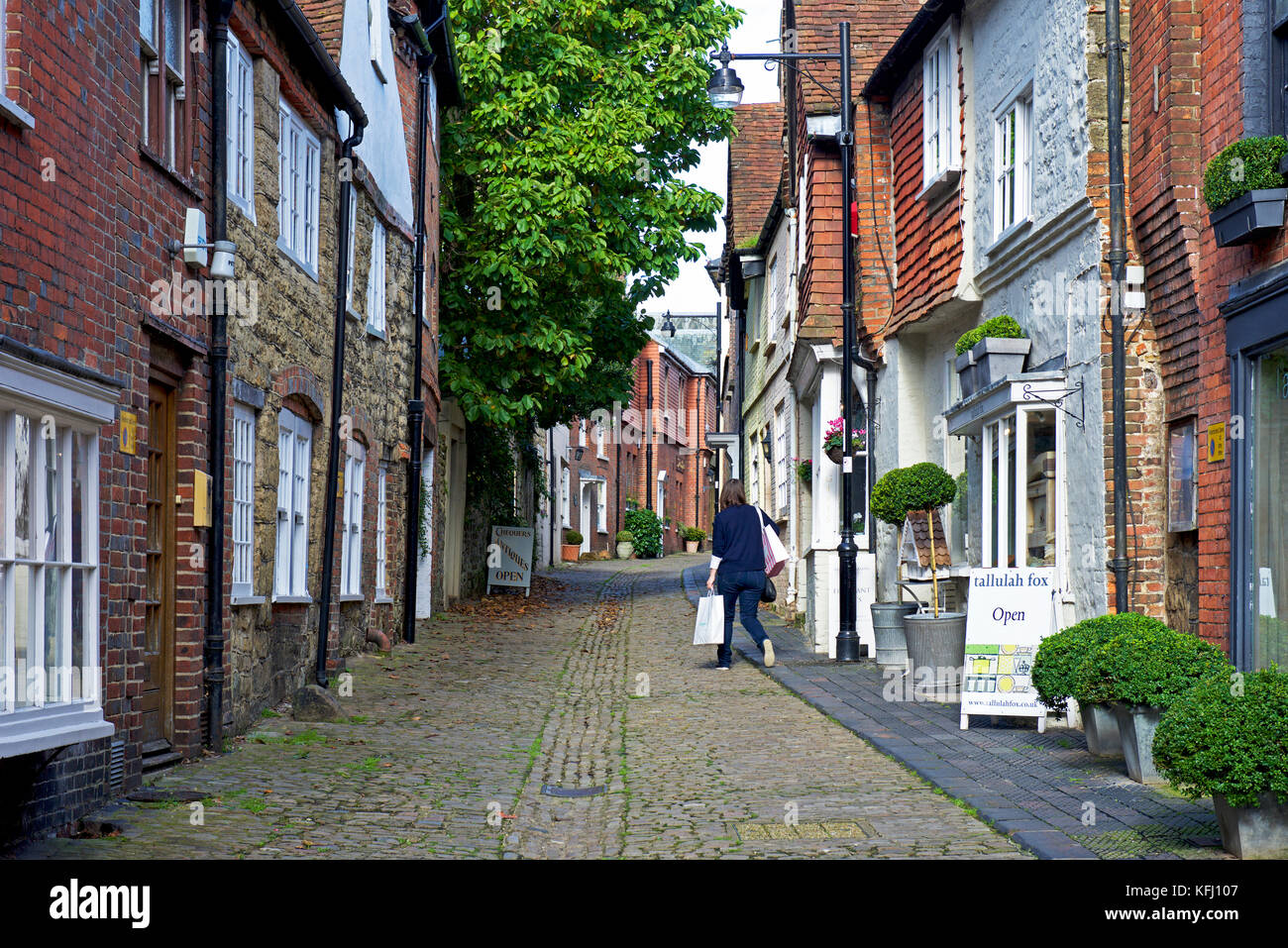 Woman shopping in cobbled Lombard Street in Petworth, a small town in east Sussex, England UK - Stock Image