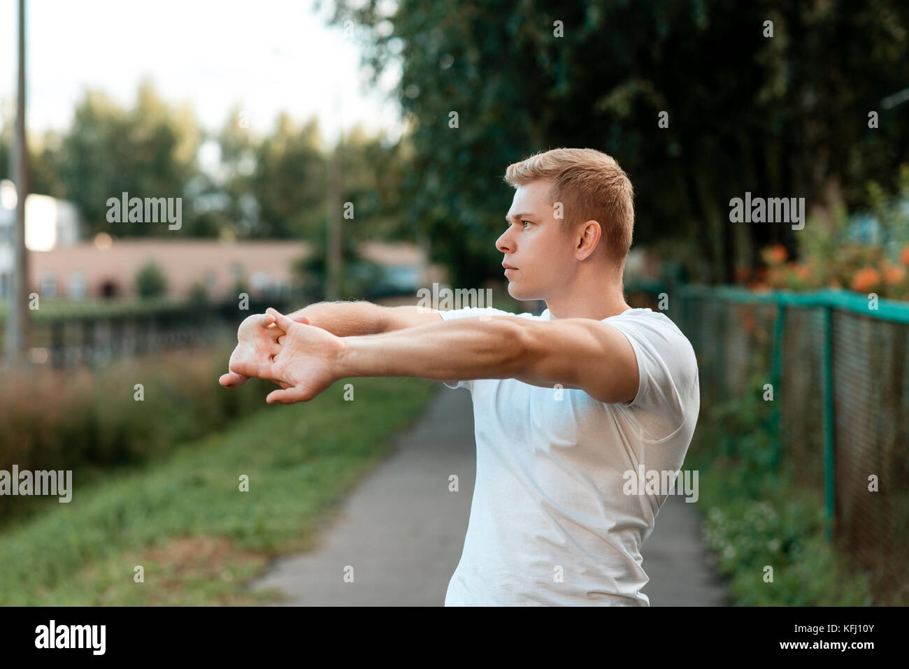 Male athlete warm-up in nature, street in the city, warming up the muscles of the hands. In the summer in the park. - Stock Image