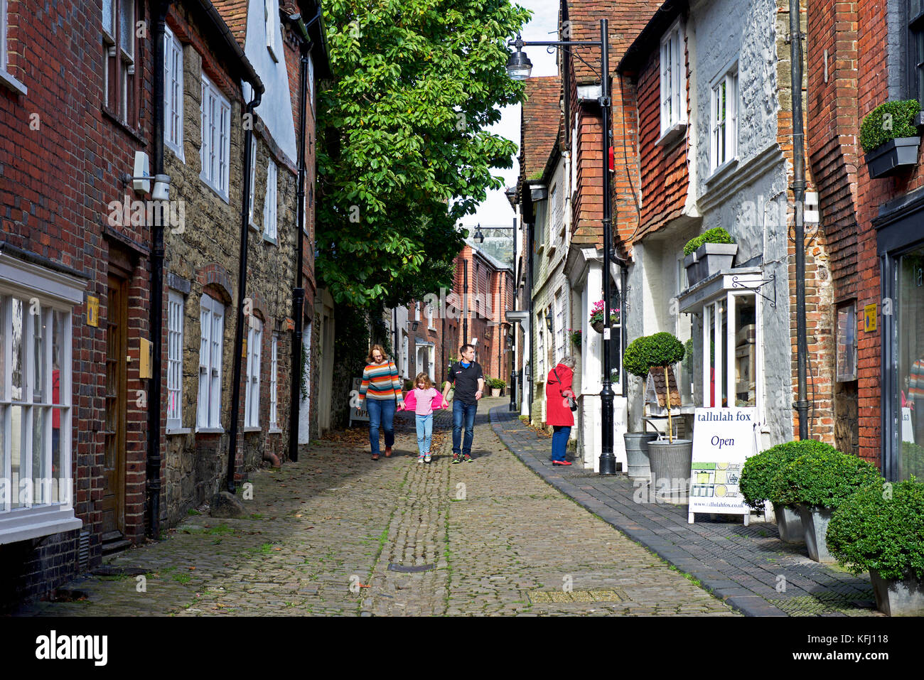 Family walking down cobbled Lombard Street in Petworth, a small town in West Sussex, England UK - Stock Image