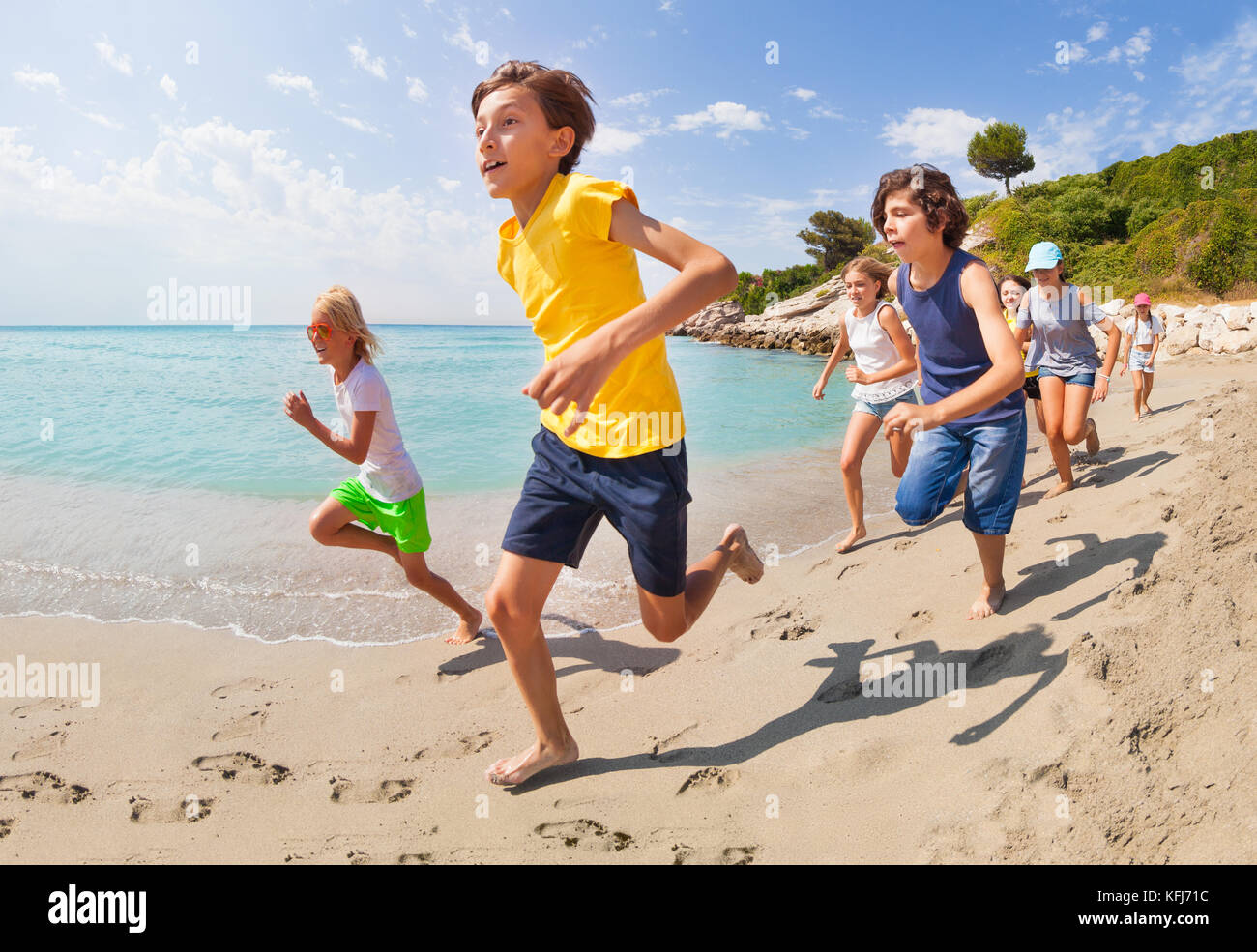 58438c5066 Running along the beach sea edge large group of kids boys and girls on  summer hot day