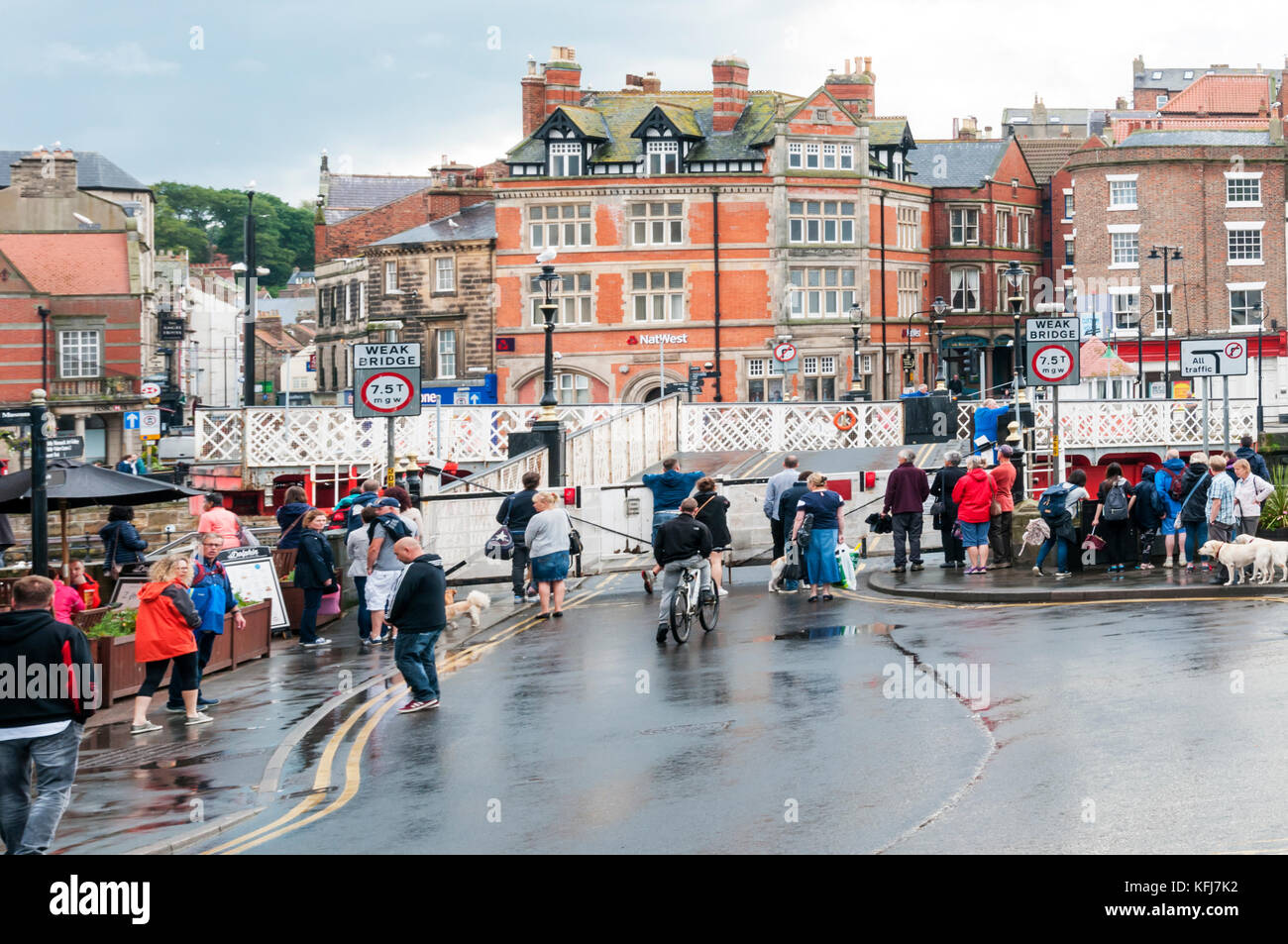 Pedestrians waiting for the swing bridge across Whitby harbour to open. - Stock Image