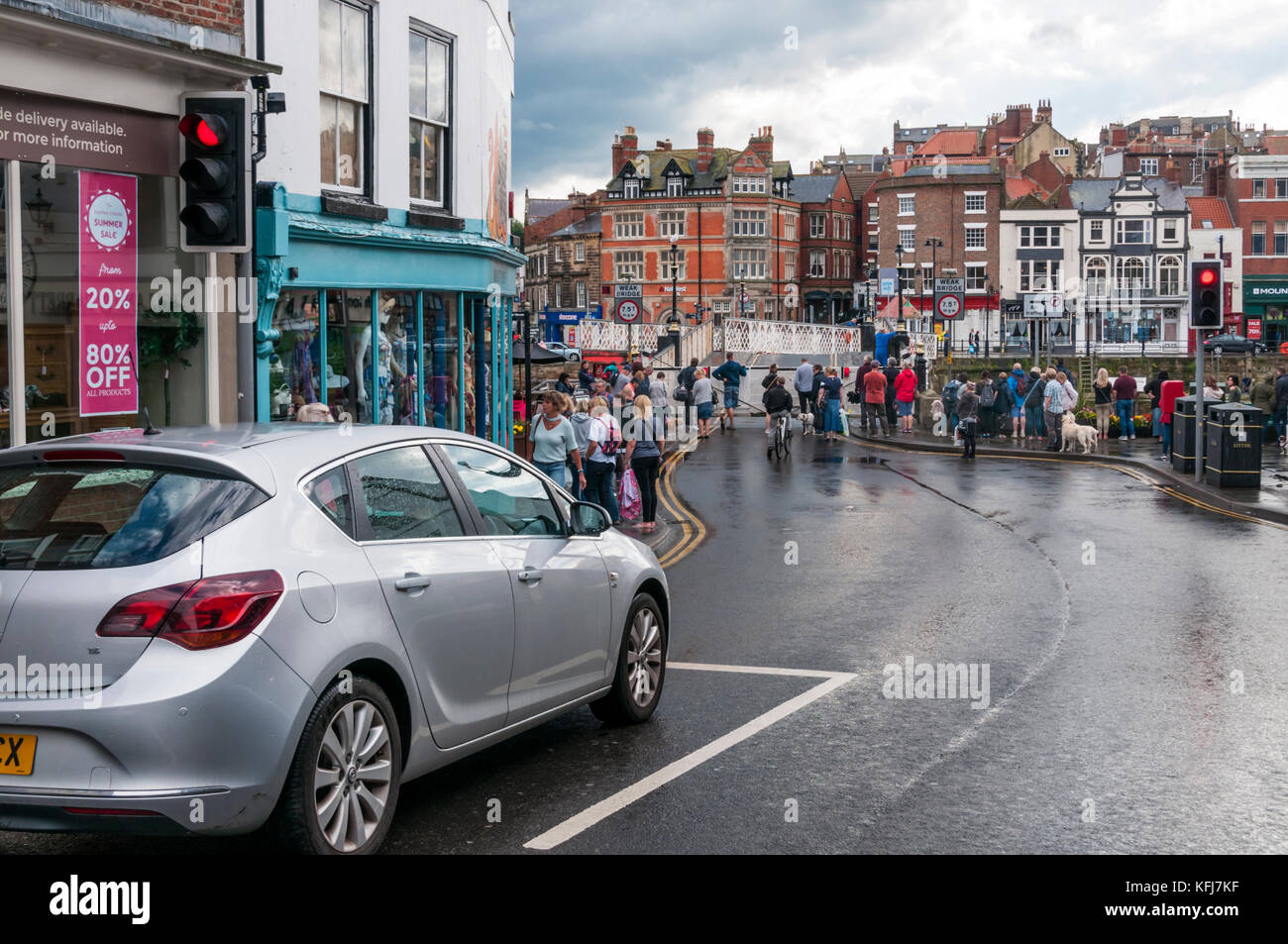 Cars and pedestrians waiting for the swing bridge across Whitby harbour to open. - Stock Image