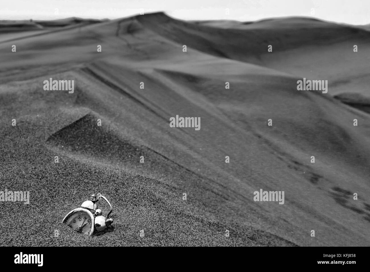 an abstract consept shot of a clock sinking in sand sorrounded by desert dunes meaning the passing of time Stock Photo