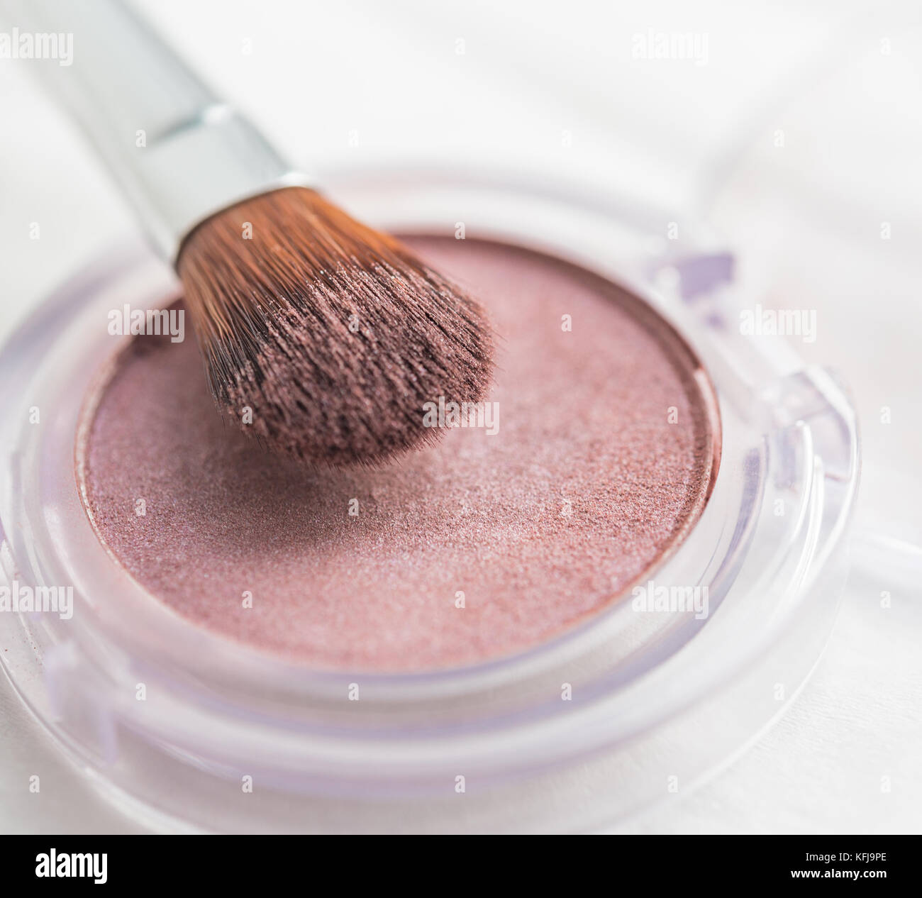 Pink pearlescent eyeshadow and brush in a transparent round pot - Stock Image