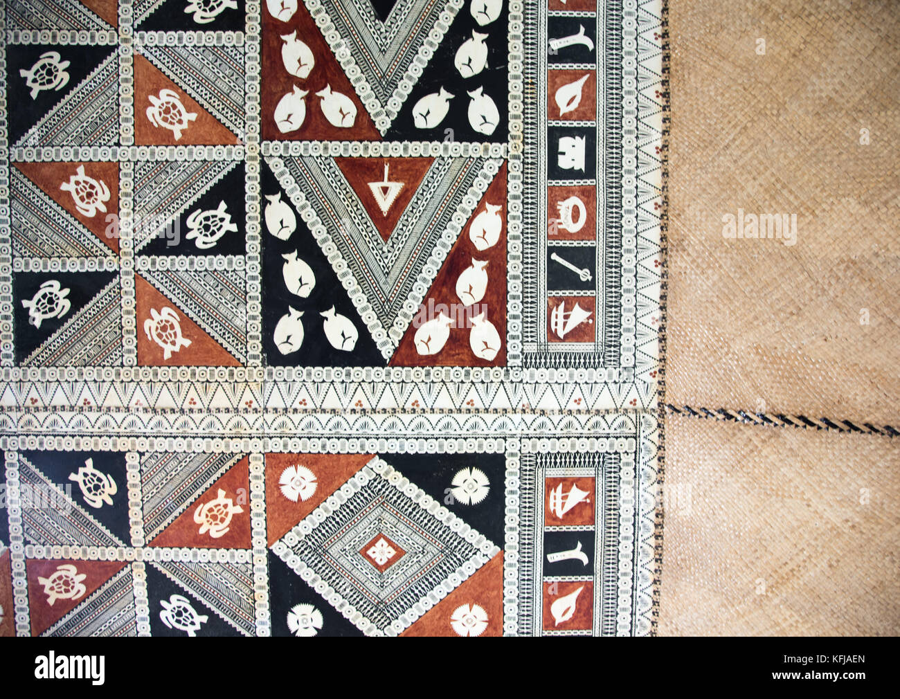 Woven textile with painted imagery in detail and repeated patterns from Suva, Fiji - Stock Image