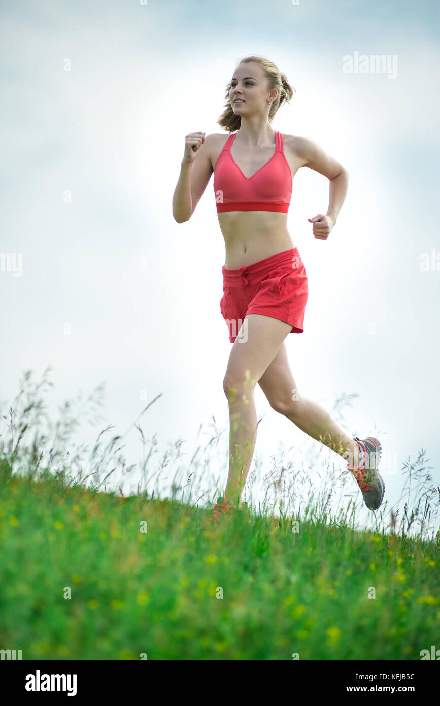 Young woman running summer park rural road. Outdoor exercises. J Stock Photo
