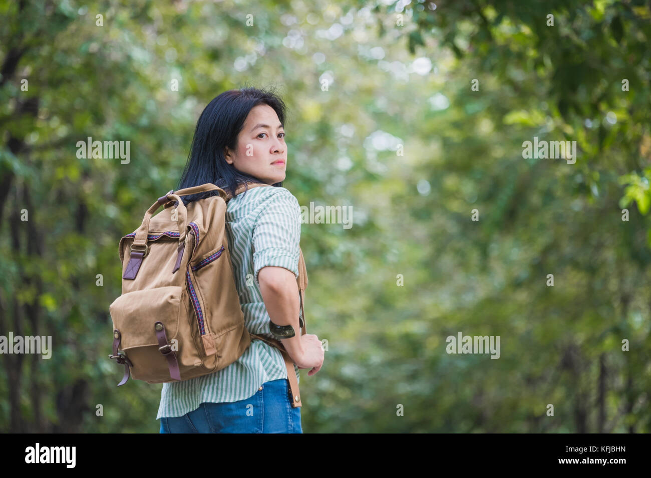 Happy young traveler woman backpacker travel in green natural forest ,greenery fresh air,Freedom wanderlust concept,Alone Stock Photo