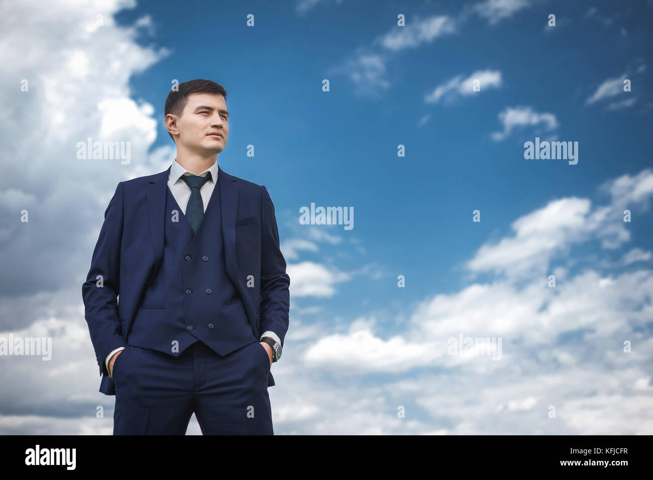 Thoughtfull groom in a blue suit smiling in the nature - Stock Image