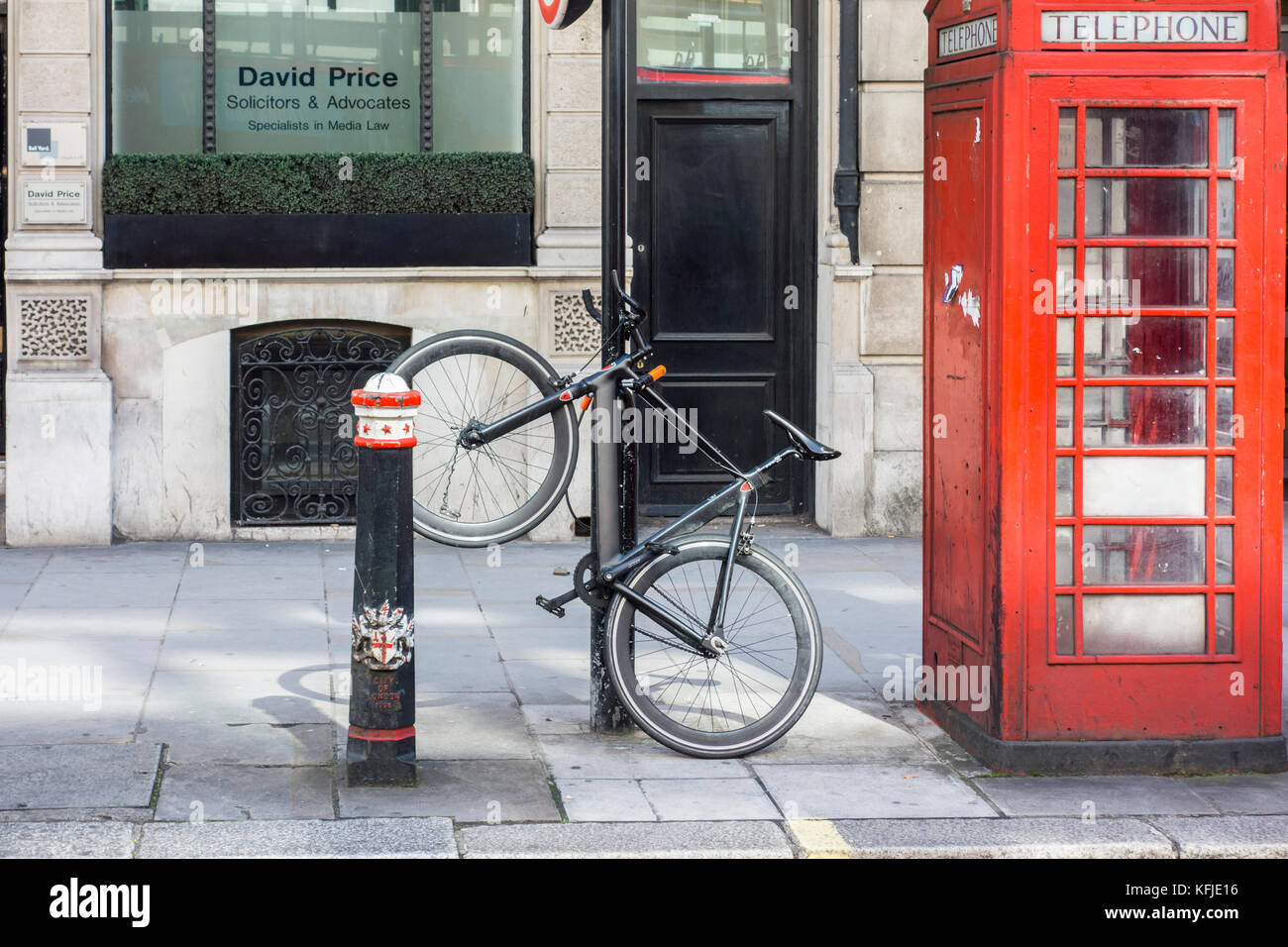 Bike parked locked secured to a post bollard next to a red telephone box, City of London, UK - Stock Image
