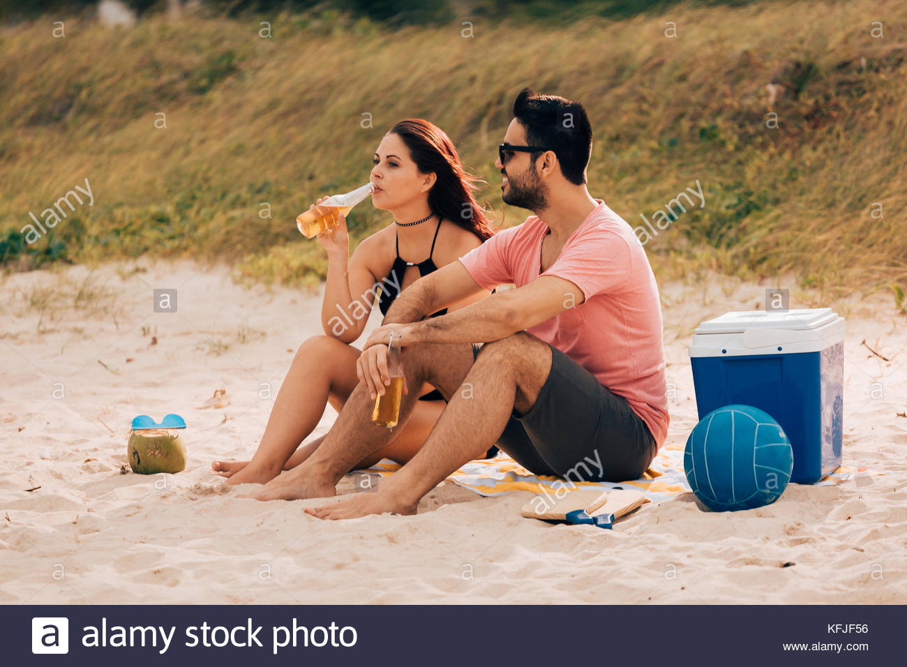 Couple drinking beer and having fun on the beach - Stock Image