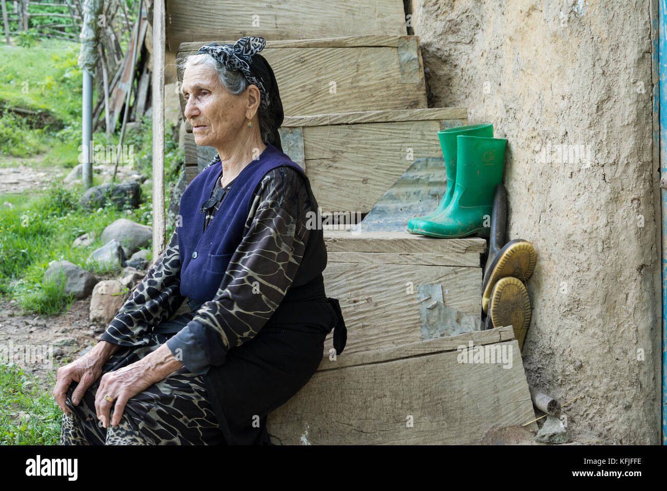 Gilan Province- IRAN-May 10, 2017 Woman seated on wooden steps and satre at outside of the frame in traditional - Stock Image