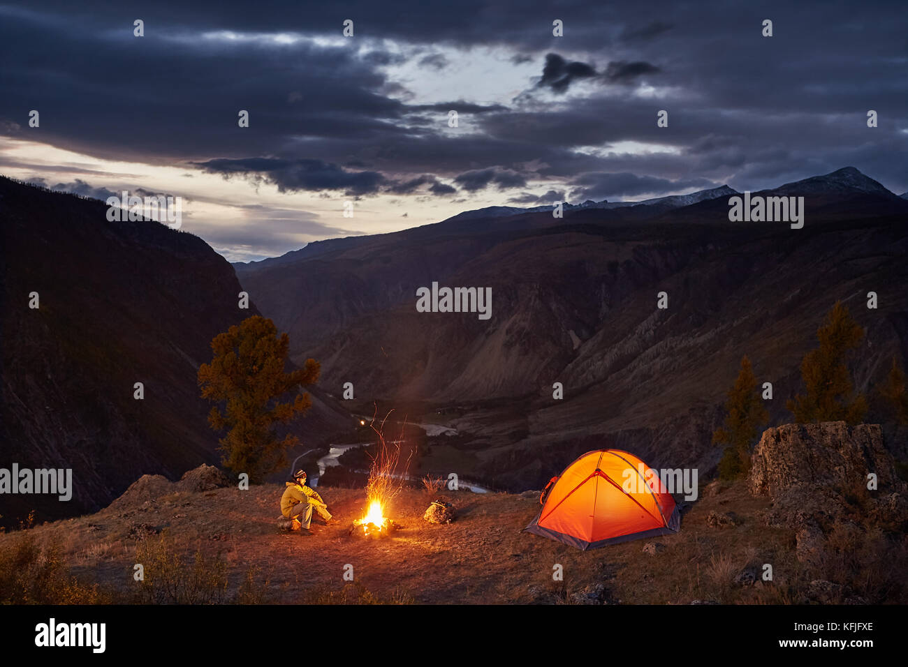 A man near illuminated tent and campfire in mountains in dawn - Stock Image