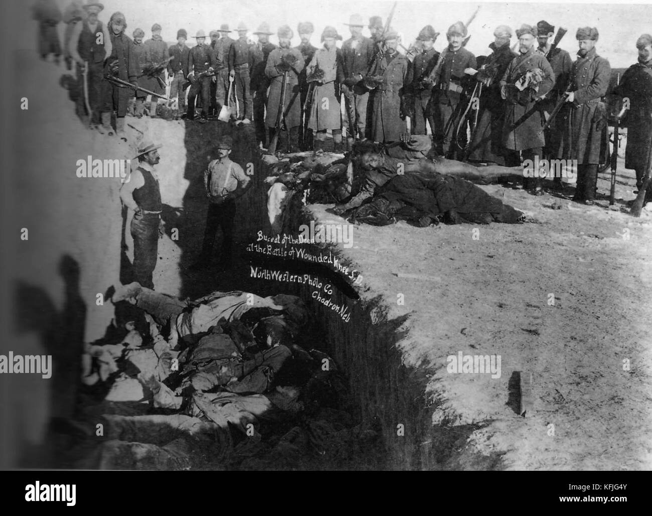 Burial of the dead after the massacre of Wounded Knee. U.S. Soldiers putting Indians in common grave; some corpses Stock Photo