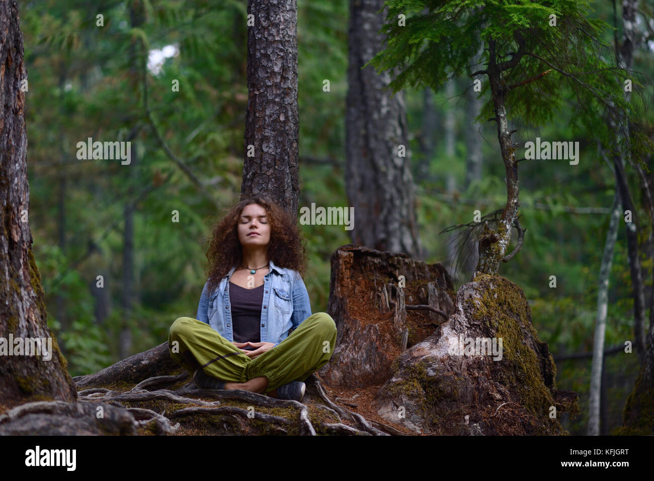 Young woman resting in a forest sitting in meditation posture leaning against a tree trunk in beautiful tranquil - Stock Image