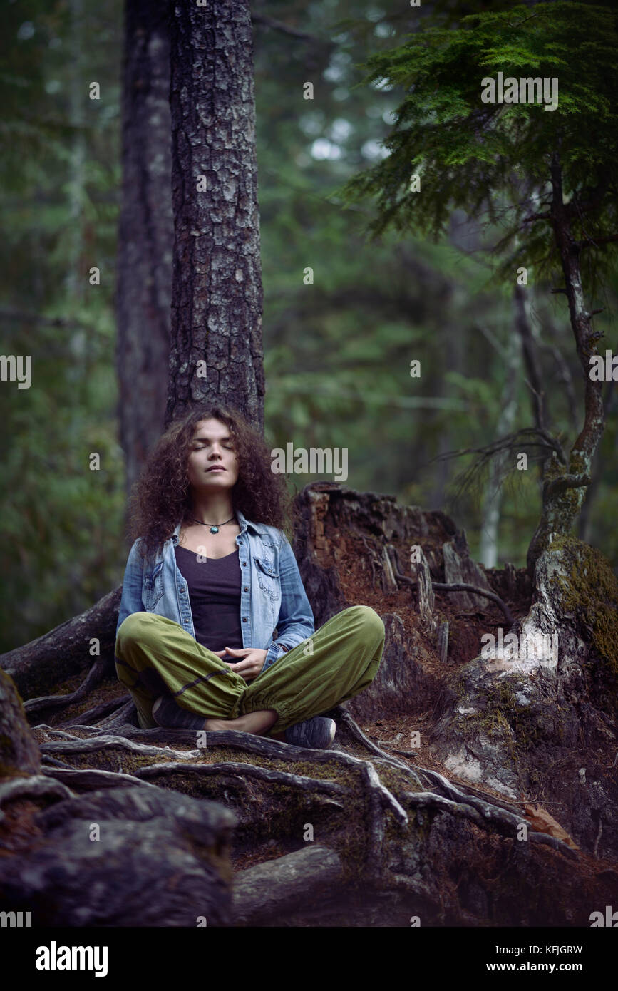 Young woman meditating in a forest sitting in meditation pose with her legs crossed leaning with her back against - Stock Image