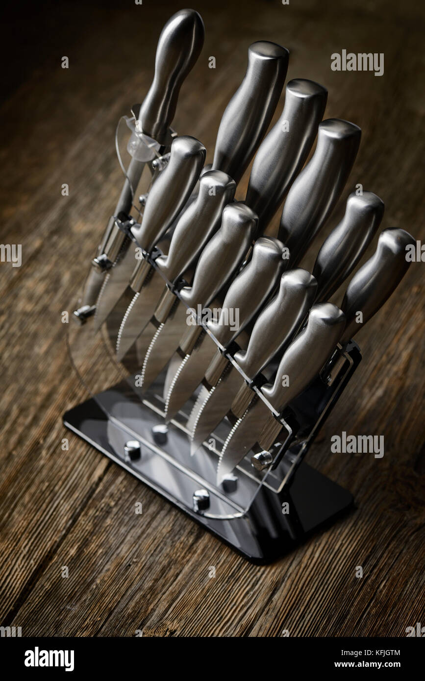 Modern steel kitchen knives set in a knife block on rustic wood background - Stock Image