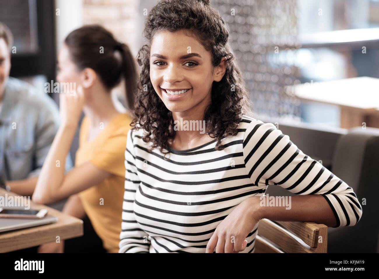 Attractive alert curly-haired dark-eyed girl smiling - Stock Image